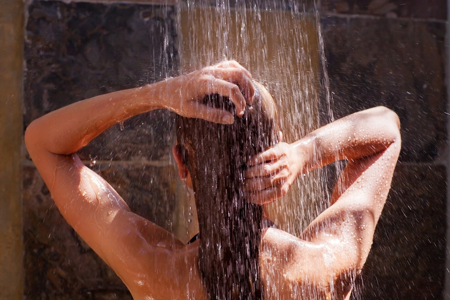Woman in the shower, back side of young female showering under r