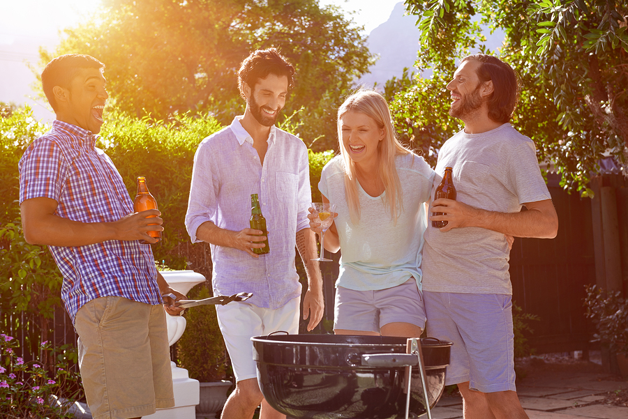 group of friends having outdoor garden barbecue laughing
